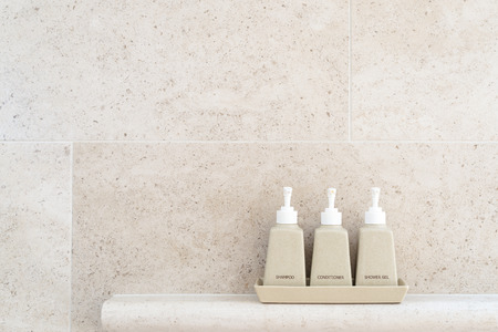 Toiletries tube in a luxury hotel, shower gel, shampoo and hair conditioner in ceramic ware. Copy space.