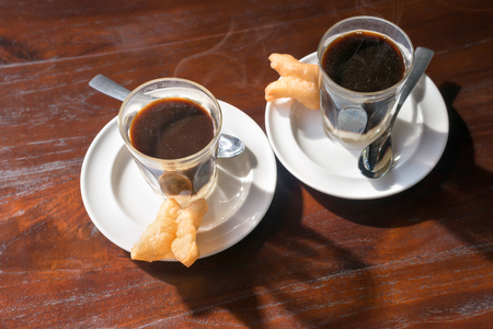 sweetened: Thai tradition hot coffee with sweetened condensed milk in old style cup, served on wooden table. Stock Photo