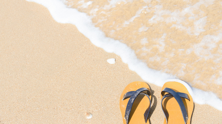 swimming shoes: Tropical vacation concept - sandal on a sandy beach