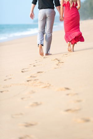 Couple walking on the beach with footprints on sand. Copy space.