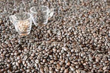 Geröstete Kaffeebohnen mit verschwommen 2 Kaffeetassen auf den Hintergrund. Standard-Bild - 60100790