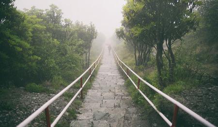 Einsam im regen, eine frau in schwarzen tüchern mit bedeckung rotem regenschirm, der die stein treppe im regen und nebel hinunter geht Standard-Bild - 60100804