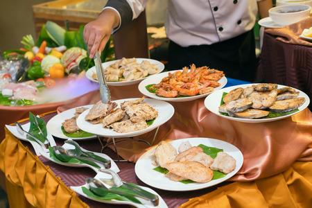 Chef, der Platten von verschiedenem Fleisch, von Schweinefleisch, von Rindfleisch, von Huhn, von Fischen, von Garnele und von Tintenfisch zum Abendessen in einem Luxusrestaurant vorbereitet. Standard-Bild - 62465424