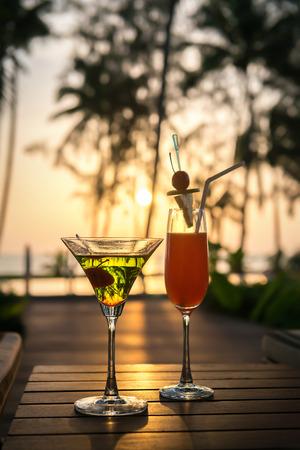 Bunte Cocktails auf Holztisch und Sonnenliegen am Pool Zugang vorne, Strand Meerblick bei Sonnenuntergang. Standard-Bild - 62466056