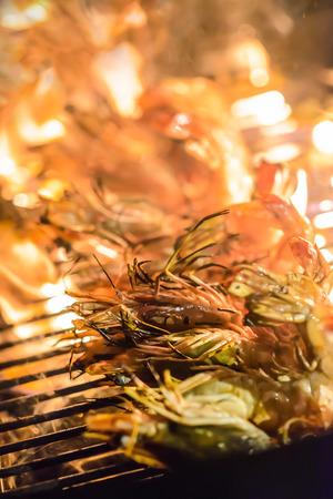 Gegrillte Garnelen auf dem Grill mit Flammen im Hintergrund, selektiven Fokus. Standard-Bild - 62466064