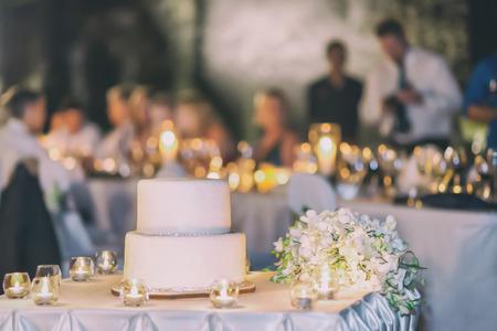 Der einfache weiße Kuchen, dekoriert mit dem silbernen Boden, Kerzenlicht auf Party Hintergrund. Standard-Bild - 62466074