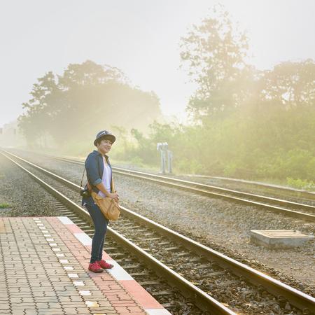 In einem nebeligen Sonnenschein Tag eine asiatische Frauen , die auf einem Zug auf der Plattform auf der lokalen Bahnstation warten Standard-Bild - 62466364