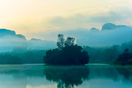 Kleine Insel auf einem leicht nebligen am frühen Morgen Standard-Bild - 62466405
