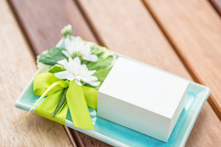a small white box on decorated turquoise ceramic tray with white flowers and green ribbon