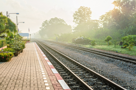 Beautiful sunshine foggy morning at platform of local Thailand train station. Text space. Stock Photo