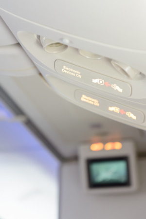 Electronic devices off and fasten seat belt sign inside airplane.
