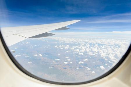 Land Wolken und Himmel durch das Fenster der Flugzeugkabine gesehen. Standard-Bild - 62466954