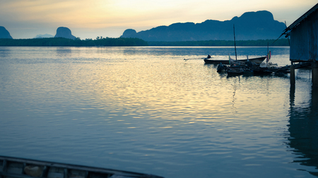 phangnga: Long tail fishing boat at Samchong fishing village on sunrise in Phang-Nga,Thailand. Stock Photo