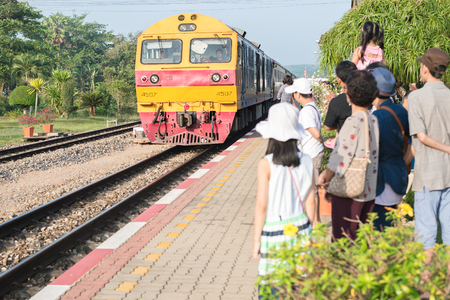 Chumphom, Thailand - March 31, 2015: Passengers from behind standing at platform before entering train in Chumphon, Thailand.