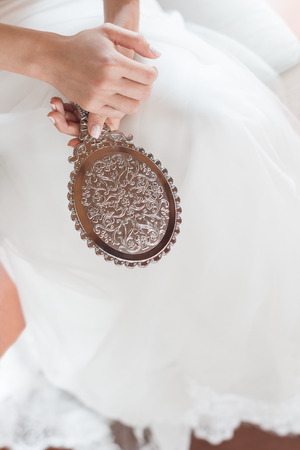 Bride join hands with antique pattern mirror on her white wedding dress.