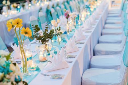 ロマンチックなディナーのセットアップ、キャンドル ライト、ランタン、花で飾られた白と青のテーマ。選択と集中。