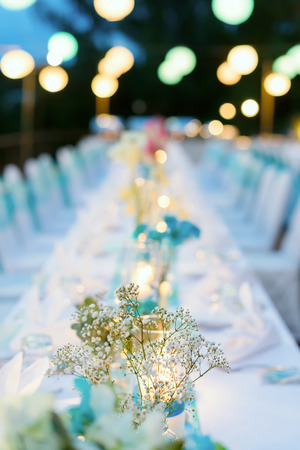 Romantic dinner setup, White and Blue theme decorated with candle light, lanterns and flowers. Selective focus.