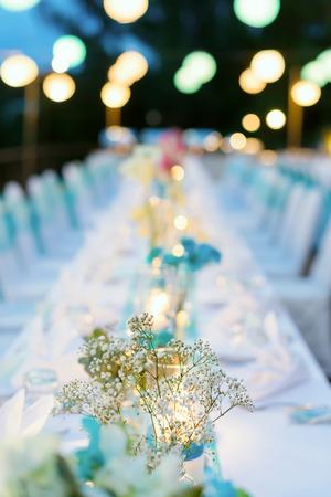 Romantisches Abendessen Setup, weiß und blau Thema dekoriert mit Kerzenlicht, Laternen und Blumen. Selektiver Fokus. Standard-Bild - 65331313