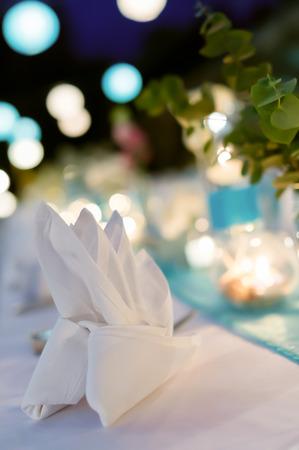 Romantisch diner setup, wit en blauw thema gedecoreerd met kaarslicht, lantaarns en bloemen. Selectieve aandacht. Stockfoto