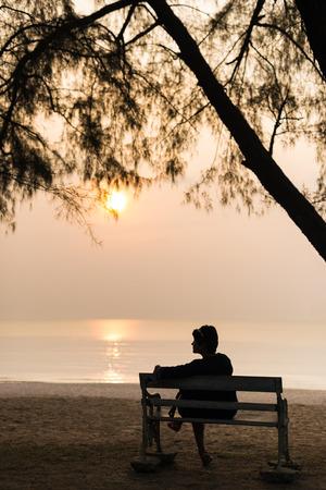 孤独、ビーチにサンセットでレトロなベンチに彼女のバッグを一人ぼっちで座ってシルエット女性旅行者。