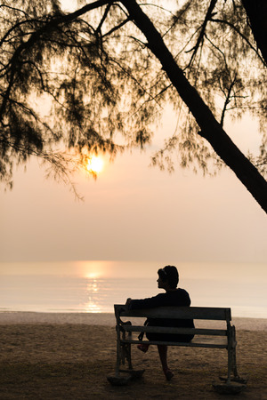 eenzaamheid, silhouet vrouw reiziger zit alleen met haar tas op retro bank bij zonsondergang op het strand.