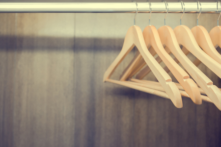 Clothes hanger in wardrobe. Vintage process. Close up with copy space.