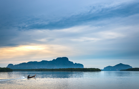 Fishermen out for fishing in every morning with longtail fishing boat at Samchong-Tai fishing village on sunrise in Phang-Nga, Thailand.