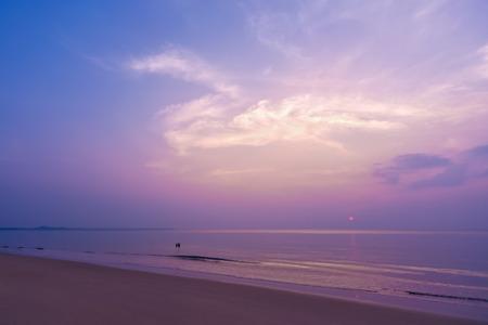 ロマンチックな夕日、カラフルな甘い空、魔法の雲、熱帯のビーチでカップル。
