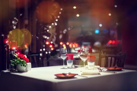 ロマンチックなディナーのセットアップまたは光、キャンドルが付いて赤い装飾の設定休日テーブル。 写真素材