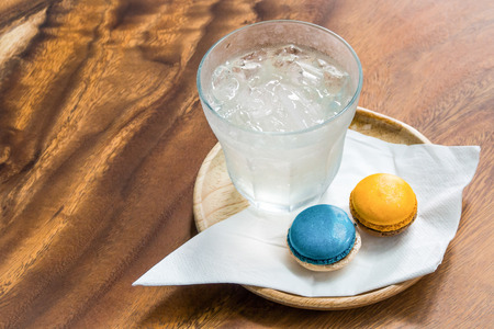 Welkomstdrankje met verse ijswater, blauwe en oranje kleuren magaroons en witte nepkin in houten bakje op houten tafel. Stockfoto