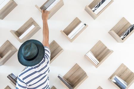 Een man is op zoek naar het boek dat hij wil in een prachtig versierde bibliotheek met een boekenplank en een rotanstoel.