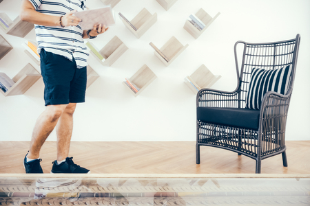 A man is searching for the book he wants in a beautifully decorated library with a bookshelf and rattan chair.