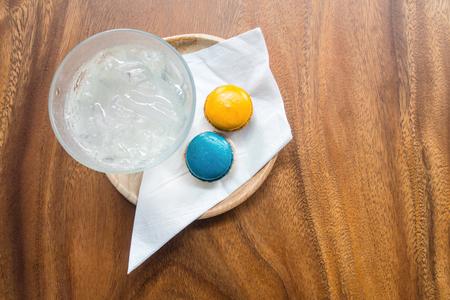 ウェルカムド リンク セット新鮮な氷-水、青とオレンジ色の木製テーブル木製のトレイに magaroons と白 nepkin。