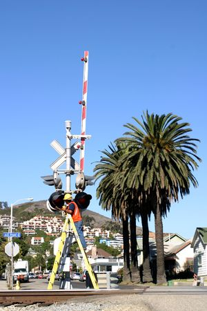 Man cleaning the rail road crossing signals photo