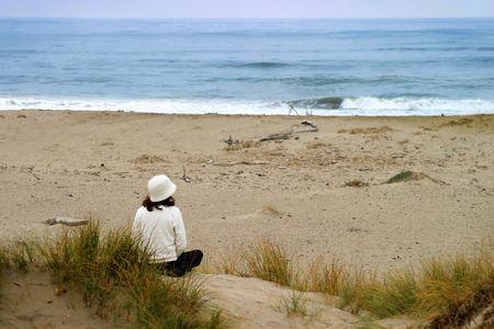 Junge Frau sitzt am Strand Blick über den Ozean Standard-Bild - 2547304