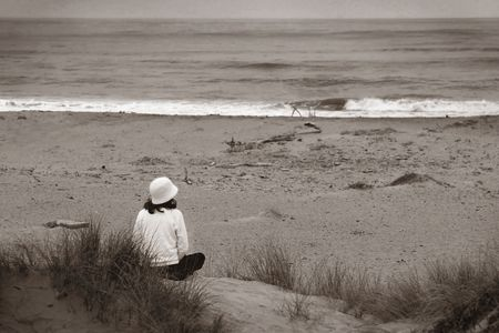 Young woman sitting at the beach looking over the ocean photo