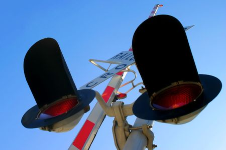 Railroad Crossing signal from below with sky in the background photo