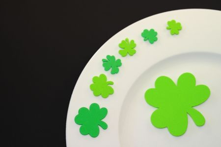 White plate on black background with green clover leafs. Stock Photo - 2684969