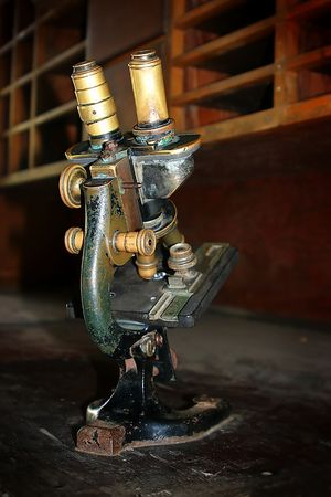 Aged microscope standing on an old wooden secretary. photo