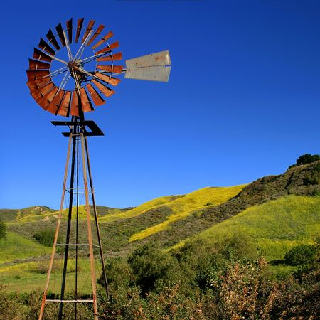 Windmill with a green and yellow spring field in the background. photo