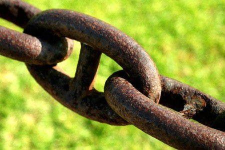 Old rusty chain with green grass in the background. Stock Photo - 4121730
