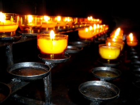 mood moody: Burning candles in a church for worship.