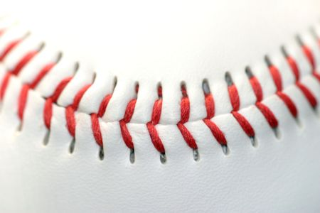 Close up of a white baseball with red seams photo