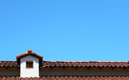 attic: Roof top with small window and a blue sky in the background