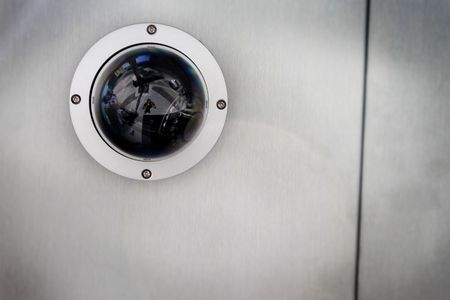 Round security camera in a silver metal ceiling.