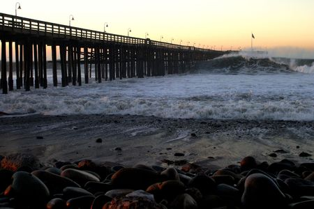 throughout: Ocean waves throughout at storm crashing into a wooden pier.