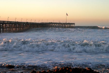Ocean waves throughout at storm crashing into a wooden pier. photo