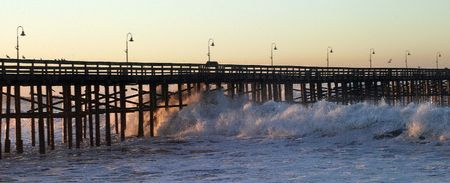 Ocean waves throughout at storm crashing into a wooden pier.