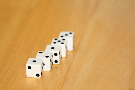 six objects: five black and white dice on a wooden background