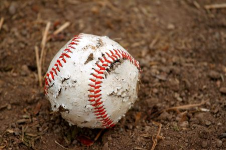Old red and white rugged baseball on a dirt ground photo